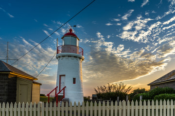 Lighthouse at Sunset. Romantic historic lighthouse in Warrnambool Australia, taken during sunset. Wooden fence in the foreground. Colorful sky.