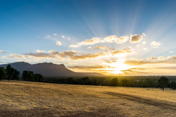 Idyllic Grampians Sunset. Sunset at Grampians National Park Australia. Dry yellow grass in the foreground, eucalyptus forest and iconic mountain in the background.