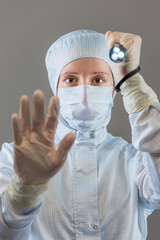 chemist with a flashlight shows STOP gesture hand on a gray back