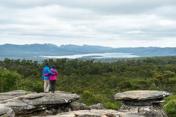 Couple looking at Stunning Grampians National Park View. Older couple standing arm in arm looking at eucalyptus forest and distant lake.