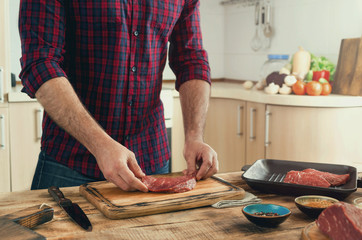 Man cooking grilled beef steak on the home kitchen