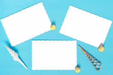 three sheets of white paper on a blue background with shells