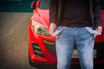 Man showing his empty pockets with red car background.