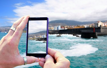 View over the mobile phone display during shooting of Tenerife coast. Holding the mobile phone in hands and taking a photo, focused on mobile phone screen.