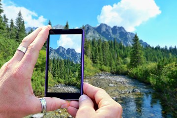 View over the mobile phone display during shooting nature of High Tatras. Holding the mobile phone in hands and taking a photo, focused on mobile phone screen.