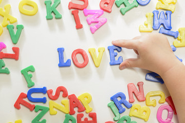 Little girl learning to write using magnetic letters. Learn Study Education School Knowledge Concept