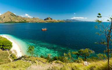 Komodo Coral Bay Viewpoint. View over white sand beach and coral bay at Komodo, Flores Indonesia. Grass in the foreground and mountains in the background.
