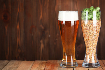 Glasses with beer, hops and malts on wooden background