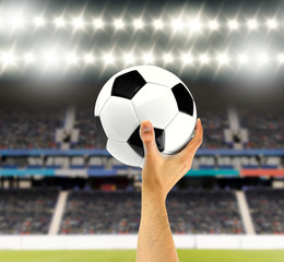 Classic soccer ball in hand of man at stadium