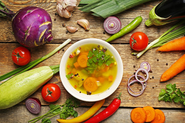 Soup and fresh vegetables on wooden background