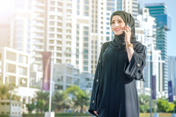 Smiling businessman talking on a cell phone in Dubai. Arab hijab