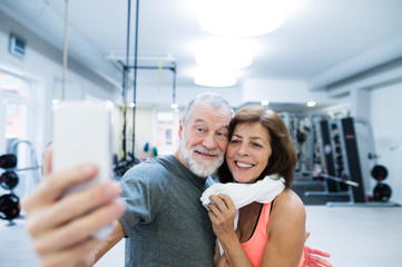 Senior couple in gym resting, taking selfie with smartphone