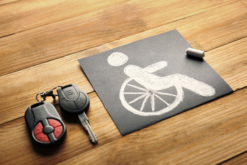 Car key and chalkboard with handicap sign on wooden background
