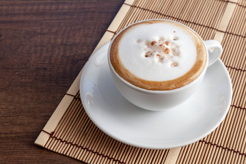 Wall Mural - Coffee cup of cappuccino on bamboo mat, on wooden background wit