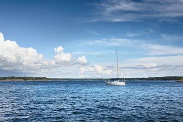 Small sailboat sailing against Finland shoreline