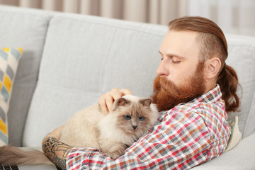 Young bearded man with fluffy cat sitting on sofa