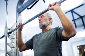 Senior man in gym doing pull-ups on horizontal bar.