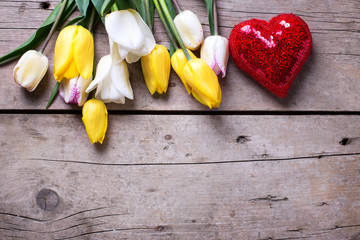 Border from spring tulips and shiny decorative heart on aged woo
