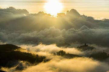 Mount Rinjani Cloudy Sunset View. View down the outside ridge of Gunung RInjani Volcano Crater, Lombok Indonesia. Sun is shining through the clouds, grassy mountain ridge.