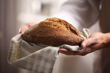 Male hands holding freshly baked rye bread, closeup