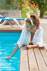 Portrait of beautiful girl listening to music in the swimming po