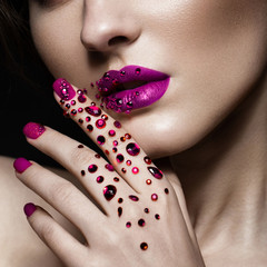 Beautiful girl with evening make-up, purple lips in rhinestones and design manicure nails. beauty face. Photos shot in studio. Close up