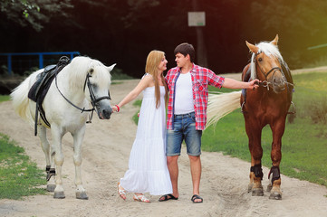 young couple walking with horse