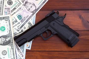 Black gun on money background