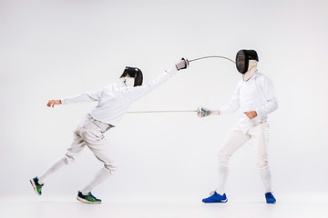 The two men wearing fencing suit practicing with sword against gray