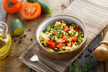 Couscous with tomatoes, cucumber and onion in a bowl for healthy breakfast. Traditional Israeli food Ptitim with vegetables. Moroccan cuisine meal. Top view.