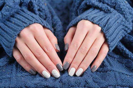 Woman hands with beautiful winter trend knit sweater manicure