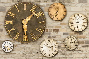 Vintage clocks hanging on an old brick wall
