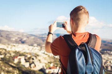 Back view of a young man tourist with backpack taking photo of landscape with smartphone
