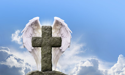 Angel Wings and Rustic Cross - highly detailed Angel Wings either side of a rustic stone cross with a bright sunny blue sky background and fluffy clouds behind with plenty of copy space