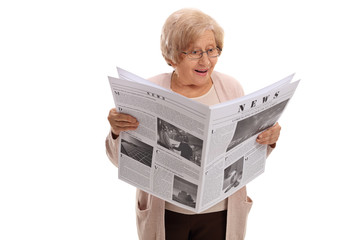 Surprised elderly woman reading a newspaper