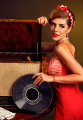 Retro woman with music vinyl record and gramophone. Pin-up retro female style. Girl pin-up style wearing red dress