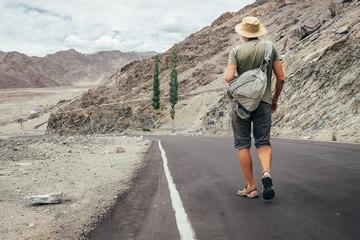 Alone traveler walks on the mountain road in indian Himalaya mou