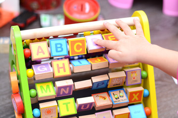 Close up of toddler's hands playing with colorful educational toy