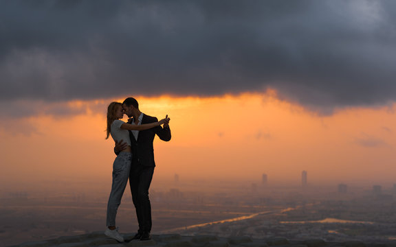 Two lovers dancing/embracing on top of a skyscraper overlooking the city at sunset. Romantic setting.