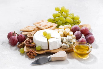 camembert, grapes and crackers on a white table