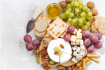 camembert, grapes and snacks on a white background, top view