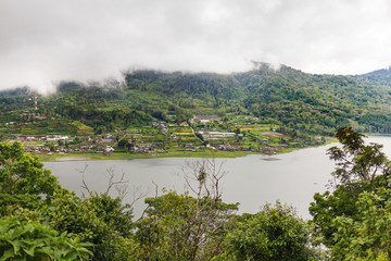 Panorama view on agricultural fields near Batur volcano, Kintamani. Winter rainy and cloudy season. Bali, Indonesia.