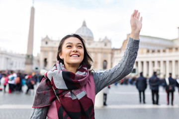 Close up portrait of young attractive woman with long dark hair on the city. She smiles and waving to somebody behind the camera.