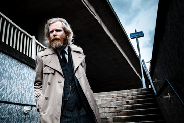 Bearded man in suit and overcoat walking down steps into a subway.