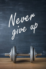 metal barbell on dark gray background and motivation text never give up