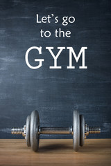 metal barbell on dark gray background and motivation text let's go to the gym
