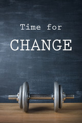 metal barbell on dark gray background and motivation text time for change