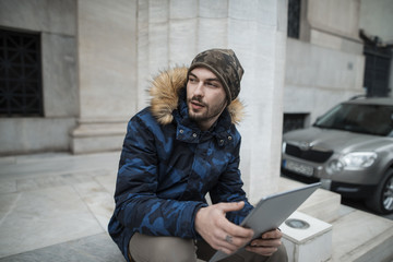young man dressed in khaki fashion and a blue camo jacket is holding a tablet pc, urban environment