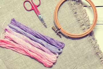 Set for embroidery. Embroidery thread shades of violet and pink color, embroidery hoop, scissors and needle on linen homespun cloth. Coloring and processing photos. Shallow depth of field.