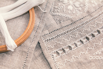 Set for embroidery. Embroidery thread white color, embroidery hoop and needle on linen with needlework in progress. Coloring and processing photos. Shallow depth of field.